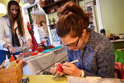 Monica Maschak - mmaschak@shawmedia.com Comfy Cottage's Meredith Bodiger (right) personalizes miniature Christmas mugs in the Ridgefield antique shop on Saturday, November 24, 2012.  The shops in Ridgefield officially welcomed the holiday season by hosting their Kris Kringle Days event.