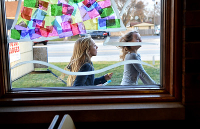 Monica Maschak - mmaschak@shawmedia.com Fifth-grader Lily Muse (left) and fourth-grader Raegan Stinger run back inside after checking the progress of their decorations on the windows of Paulee's Pizzeria in Wonder Lake on Tuesday, November 27, 2012. Muse and Stinger are part of the Muse Art Club for K-5th grade at Harrison Elementary School.  The club was asked to decorate the pizzeria and the Chamber of Commerce in preparation for Winter Wonder Walk on Saturaday, December 1, 2012.