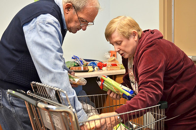 Monica Maschak - mmaschak@shawmedia.com Volunteers John Drapanes (left) and Marilyn Calvin unload a client's cart before bagging the items at the Harvard Food Pantry and Senior Center on Tuesday, Novemer 27, 2012.  The food pantry will receive a Governor's Hometown Award on Thurday for being built and paid for entirely by community members and volunteers last year.
