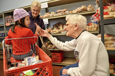 Monica Maschak - mmaschak@shawmedia.com Gerry Baumann, a Harvard Food Pantry volunteer, hands a granola bar to four-year-old Lilliana Rios who came to the food pantry with her great-grandmother Janice Traviss on Tuesday, November 27, 2012.  The Harvard Food Pantry and Senior Center will receive a Governor's Hometown Award on Thurday for being built and paid for entirely by community members and volunteers last year.