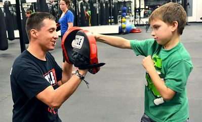 Monica Maschak - mmaschak@shawmedia.com Eight-year-old Ethan Paganelis (right) practices jabbing with trainer Jose Alanis while he waits for his mom's boxing class to finish at Title Boxing Club in Crystal Lake on Tuesday, November 27, 2012.