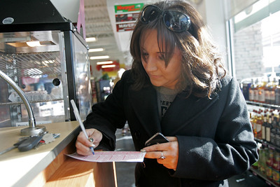 Monica Maschak - mmaschak@shawmedia.com Lottery player Maria Zarate fills out a Powerball Play Slip at a Thornton's gas station in Cary on Wednesday, November 28, 2012.  A play slip allows its players to select numbers of their choice to match the numbers drawn for the jackpot at 9:59 p.m. Wednesday night.