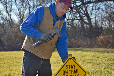 Monica Maschak - mmaschak@shawmedia.com Gary Manuel, with the Richmond Trailblazers, hammers a safety sign into the ground for snowmobile riders along a trail in Richmond on Wednesday, November 28, 2012. The McHenry County trails, located on private land, will open on December 10, 2012 at the earliest.
