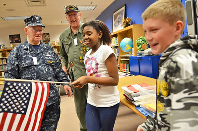 Monica Maschak - mmaschak@shawmedia.com Navy veteran John White (left) and Army Veteran Jim Mertz handed out flags to their Lincoln Prairie Elementary fifth grade student helpers Selena Chitambo and Daniel Zust after they practiced how to properly fold an American Flag on Friday, November 30, 2012. White and Mertz are members of the Lake in the Hills American Legion Post 1231 and give presentations on the history of the American Flag to elementary schools and other organizations year round.