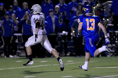 Sarah Nader - snader@shawmedia.com Cary-Grove's Kyle Norberg (left) runs past Lake Forest's Charles Moss to score a touchdown during the third quarter of  Saturday's Class 6A semifinal gameon November 17, 2012 in Lake Forest. Cary-Grove won, 42-21.