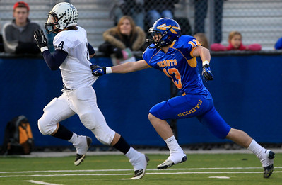 Sarah Nader - snader@shawmedia.com Cary-Grove's Ryan Mahoney (left) runs past Lake Forest's Charles Moss to score a touchdown during the first quarter of  Saturday's Class 6A semifinal gameon November 17, 2012 in Lake Forest. Cary-Grove won, 42-21.
