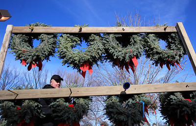 Sarah Nader - snader@shawmedia.com Chris Burns of Algonquin hangs up holiday wreaths for customers while working at the the Knights of Columbus Christmas Tree Lot at Saint Margaret Mary Church in Algonquin on Sunday, November 25, 2012. The lot opened last Friday and proceeds benefit various charities.