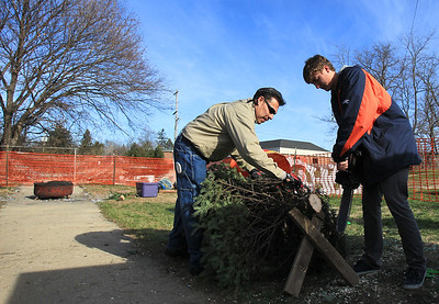 Sarah Nader - snader@shawmedia.com Rene Mendez (left) of Carpentersville and Kyle Nejman, 18, of Algonwuin wrap up a Christmas tree for a customer while working at the the Knights of Columbus Christmas Tree Lot at Saint Margaret Mary Church in Algonquin on Sunday, November 25, 2012. The lot opened last Friday and proceeds benefit various charities.