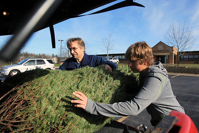 Sarah Nader - snader@shawmedia.com Tom Brey (left) of Lake in the Hills and his son, Evan, load up their Christmas tree they bought at the Knights of Columbus Christmas Tree Lot at Saint Margaret Mary Church in Algonquin on Sunday, November 25, 2012. The lot opened last Friday and proceeds benefit various charities.
