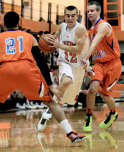 Sarah Nader - snader@shawmedia.com McHenry's Cody Freund (center) is guarded by Hoffman Estates Connor Schwarz (right) during Monday's Coaches Vs. Cancer Thanksgiving Tournament at Crystal Lake Central on November 19, 2012. McHenry was defeated, 52-62.