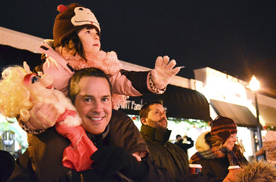 Monica Maschak - mmaschak@shawmedia.com Reagan Kauzlarich, 5, waves to a passing float as she sits on the shoulders of her dad, Tony Kauzlarich, at the Nighttime Holiday Parade in Downtown Crystal Lake on Friday, November 23, 2012.