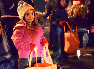 Monica Maschak - mmaschak@shawmedia.com Emma Shea Kuhn (left), 4, waits for candy along the Crystal Lake Holiday Nighttime Parade route on Friday, November 23, 2012. Parade goers awaited Santa's arrival and the lighting of the tree on Williams Street.