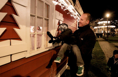 Sarah Nader - snader@shawmedia.com Jonah Aldrete of Algonquin holds his son, Ethan, 4, up so he could see inside Santa's hunt on the Woodstock Square after the Lighting of the Square in Woodstock on Friday, November 23, 2012. The event brings out a crowd of nearly 2,000 every year.
