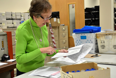 Monica Maschak - mmaschak@shawmedia.com Judy Corson, election supervisor, reads off a list of polling centers that need rubber door knob covers in the basement of the McHenry County Administration Building on Thursday, November 1, 2012.  Workers prepared and packed materials for distribution to 212 polling precincts in McHenry County.