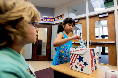 "Sarah Nader - snader@shawmedia.com Fifth grader Anthony Pizza (left), 11, of Crystal Lake watches as Sara Garcia, 6, of Crystal Lake casts her ballot for her presidential choice during a mock presidential election at Husmann Elementary School in Crystal Lake on Monday, November 5, 2012. In the past Husmann students have ""elected"" the candidate who has ultimately won the country's election."