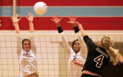 Monica Maschak - mmaschak@shawmedia.com Marion Central's Shannon Wuensch (left) and Frankie Taylor jump to block a spike from Richmond-Burton's Kim Russell in the Class 3A Sectional Championship game at Marion Central Catholic High School on Thursday, November 1, 2012.  The lady rockets defeated the lady hurricanes 2-1.