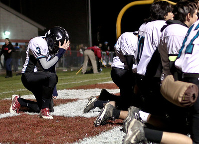 Josh Peckler - Jpeckler@shawmedia.com Woodstock North's Kyle Harr-Mathieu puts his hand on his helmet during a team meeting after being defeated by Marian Central 41-20 at Marian Central High School Saturday, November 3, 2012.