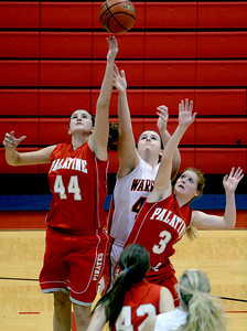 Sarah Nader - snader@shawmedia.com McHenry's McKayla Snedeker (center) and Palatine's Anna Wozniak (left) and Bridget Ryan jump for the rebound during the first quarter of Wednesday's game at Dundee-Crown High School in Carpentersville on November 14, 2012.
