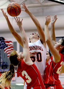 Sarah Nader - snader@shawmedia.com McHenry's Brittany Avonts (center) jumps for the rebound during the second quarter of Wednesday's game against Palatine at Dundee-Crown High School in Carpentersville on November 14, 2012.
