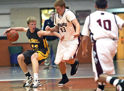 Monica Maschak - mmaschak@shawmedia.com Carmel Catholic's Michael Barr keeps Prairie Ridge's Kody Peterson at a distance while dribbling the ball in a game during the Coaches vs. Cancer tournament hosted by Crystal Lake Central High School on Saturday, November 24, 2012.  The Wolves beat the Corsairs 76-71.