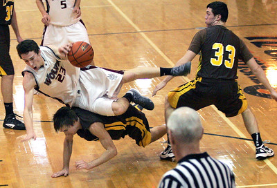 Monica Maschak - mmaschak@shawmedia.com Prairie Ridge's Steven Ticknor trips over his opponent in a game against Carmel Catholic at the Coaches vs. Cancer tournament hosted by Crystal Lake Central High School on Saturday, November 24, 2012.  The Wolves beat the Corsairs 76-71.