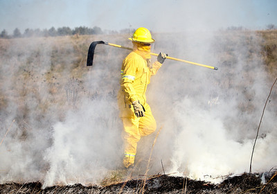 Josh Peckler - Jpeckler@shawmedia.com A firefighter with the Davey Resource Group walks through smoke during a prescribed burn at The Sanctuary of Bull Valley housing community in Woodstock Tuesday, November 13, 2012.