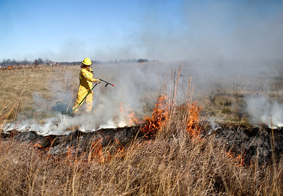 Josh Peckler - Jpeckler@shawmedia.com A firefighter with the Davey Resource Group sprays water on a prescribed burn to keep it under control at The Sanctuary of Bull Valley housing community in Woodstock Tuesday, November 13, 2012.