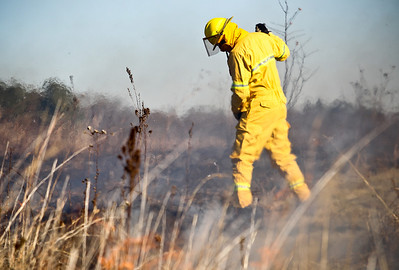 Josh Peckler - Jpeckler@shawmedia.com A firefighter with the Davey Resource Group is partially distorted by heat waves during a prescribed burn at The Sanctuary of Bull Valley housing community in Woodstock Tuesday, November 13, 2012.