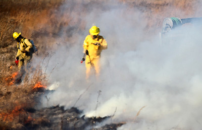 Josh Peckler - Jpeckler@shawmedia.com Firefighters with the Davey Resource Group a distorted by heat waves during a prescribed burn at The Sanctuary of Bull Valley housing community in Woodstock Tuesday, November 13, 2012.