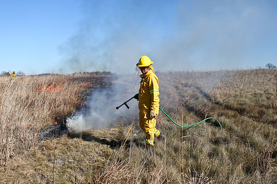 Josh Peckler - Jpeckler@shawmedia.com A firefighter with the Davey Resource Group prepares to spray water on a prescribed burn at The Sanctuary of Bull Valley housing community in Woodstock Tuesday, November 13, 2012.