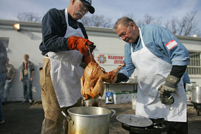 Monica Maschak - mmaschak@shawmedia.com Polish Legion of American Veterans members Mike Peterson (left) and Jim Valley check the temperature of a deep fried turkey at the VFW Post 4600 in McHenry on Thanksgiving day.  Seventy-three turkeys and 24 hams were cooked for the sailors of the Great Lakes Naval Base.