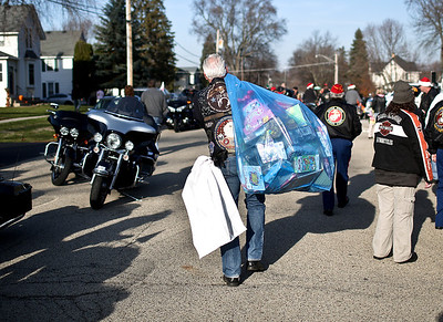 Josh Peckler - Jpeckler@shawmedia.com Joel Alger of Crystal Lake walks with a garbage bag full of toys after the Toys For Tots Christmas Parade in Mchenry Sunday, November 18, 2012. After the parade that included almost 800 motorcycle riders toys were collected to be donated to the U.S Marines Toys for Tots.