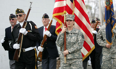 Monica Maschak - mmaschak@shawmedia.com Mike Heyl, of the Veterans of Foreign Wars Post 4600 Honor Guard, escorts the flag to the field where a rifle salute will take place during a combined Veterans Day ceremony in McHenry on Sunday.