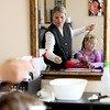 Kathy Enger, co-owner of Clean Curls in St. Charles, removes lice eggs from the hair of 4-year-old Hope Taritas of Bartlett Monday.(Sandy Bressner photo)