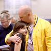 Army veteran Duane Jones hugs his daughter, Isabel, during a service for Veteran's Day at Geneva Middle School North Friday morning.(Sandy Bressner photo)