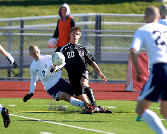 Ty Seager (20) of Wheaton Academy goes down with Peoria Notre Dame's Jerry Ivie (2) during the Warriors'  2-1 loss in penalty kicks in the IHSA Class 2A state semifinal at Lincoln-Way North High School in Frankfort Friday. (Sandy Bressner photo)