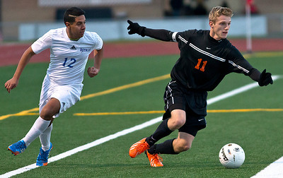 Brett Moist/ for the Northwest Herald  Mchenry's Evan Hying runs past Larkin's Chris Villalobos during the first half of the Sectional Final game at Huntley High School on Saturday. Larkin defeated Mchenry 1-0.