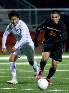 Brett Moist/ for the Northwest Herald  Larkin's Freddy Alvarez chases down the ball with Mchenry's Ovidio Jasso during the second half of the Sectional Final Game at Huntley High School on Saturday. Larkin defeated Mchenry 1-0.
