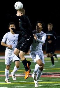 Brett Moist/ for the Northwest Herald  Mchenry's Evan Hying hits the ball with his head past Larkin's Freddy Alvarez during the second half of the  Sectional Final game at Huntley High School on Saturday. Larkin Defeated Huntley 1-0