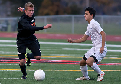 Brett Moist/ for the Northwest Herald  Mchenry James Mulhall kicks the ball past Larkin's Moises Raya during the first half of the Sectional Final game at Huntley High School on Saturday. Larkin defeated Mchenry 1-0.