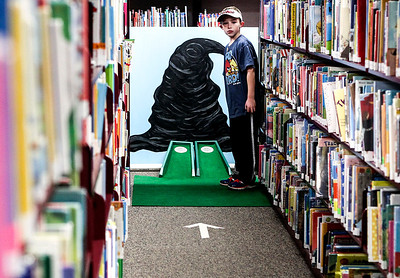 Sarah Nader- snader@shawmedia.com Brendan Busky, 8, of Algonquin watches his sister putt while attending MiniLinks at the Library hosted by the Huntley Area Public Library District Friends Foundation at the Huntley Public Library Friday, November 8, 2013. Attendees played a nine-hole round of mini-golf in the library after hours.