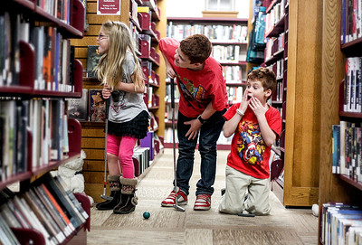 Sarah Nader- snader@shawmedia.com Emily Kellas (left), 6, of Huntley and her brothers, Parker, 12, and Liam, 8, watch as their dad putts while attending MiniLinks at the Library hosted by the Huntley Area Public Library District Friends Foundation at the Huntley Public Library Friday, November 8, 2013. Attendees played a nine-hole round of mini-golf in the library after hours.