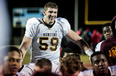 Kyle Grillot - kgrillot@shawmedia.com   Montini senior Dylan Thompson smiles with his team as he listens to his coaches after beating Marian Central in  the Class 5A second round football game Friday in Woodstock. Montini won the game 40-7.
