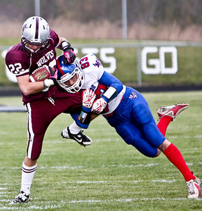 Josh Peckler - For the Northwest Herald  Prairie Ridge's David Faccone (22) is tackled by Marmion's Tyler Eberth during the third quarter of the IHSA Class 6A second round playoff game at Prairie Ridge High School Saturday, November 9, 2013.