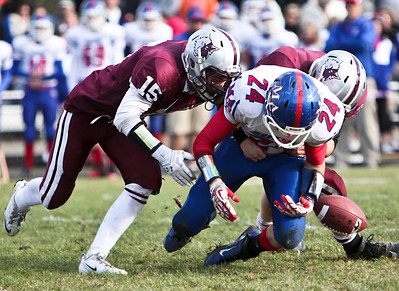 Josh Peckler - For the Northwest Herald  Prairie Ridge's Nick Gregory (15) helps knock the ball out of the hands of Marmion's Josh Meyers during the third quarter of the IHSA Class 6A second round playoff game at Prairie Ridge High School Saturday, November 9, 2013.