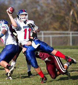 Josh Peckler - For the Northwest Herald  Marmion quarterback Brock Krrueger gets a pass off while being tackled by a Prairie Ridge defender during the third quarter of the IHSA Class 6A second round playoff game at Prairie Ridge High School Saturday, November 9, 2013.
