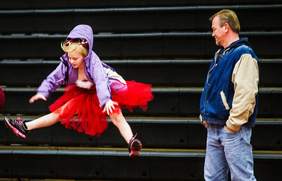 Kyle Grillot - kgrillot@shawmedia.com   Tom Wedin of McHenry watches as his daughter Steffanie Wedin jumps off of the bleachers after performing with the first and second grade Bantam poms during the first Pom and Cheer Showcase at McHenry High School West Campus Sunday. All 11 of McHenry Junior Warriors Pom and Cheer teams take turns in the spotlight, raising funds for the nonprofit McHenry Junior Warriors Pom and Cheer organization.