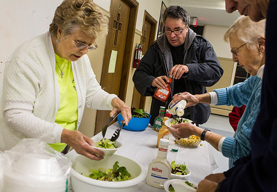 Kyle Grillot - kgrillot@shawmedia.com   Fran Parker of McHenry (left) prepares bowls of salad for visitors like Scott Grubnau (center) and Helen Brown at the 1st United Methodist Church during the Sunday Community Thanksgiving Dinner. The church has offered free dinners on the second sunday of every month for the past two years. Along with food purchased by the church, McHenry businesses and community members donate food for the meals, prepared by chef Scott Hoak.