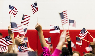 Kyle Grillot - kgrillot@shawmedia.com   Students wave flags in the air to recognize the veterans attending their Veterans Day Service Monday at Parkview Elementary in Carpentersville. The service includes a parade of students, music, the posting of colors, a rifle salute, and playing of taps in observance of Veterans Day.
