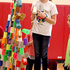 Fabyan Elementary School fifth-grader Devynn Day (standing on chair) watches as dozens of cups fall from a pyramid she built with her classmates as part of a cup sport stacking competition during her physical education class at the Geneva school Thursday afternoon.